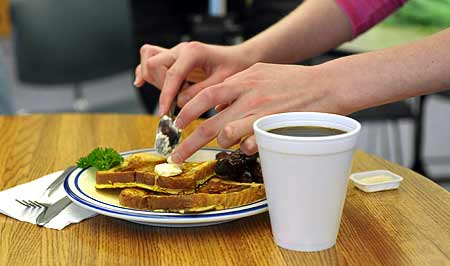 A student adds butter to French Toast to make it appear as good as it will taste before photographing it.