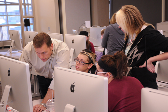 Graphic Design and Communications instructor Sean Thorenson helps students create graphics that will be used in video production.